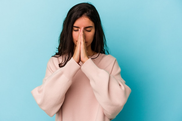 Jonge blanke vrouw geïsoleerd op blauwe achtergrond bidden, tonen toewijding, religieuze persoon op zoek naar goddelijke inspiratie.