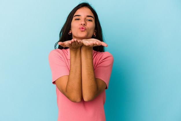 Jonge blanke vrouw geïsoleerd op blauwe achtergrond die lippen vouwt en handpalmen vasthoudt om luchtkus te sturen.