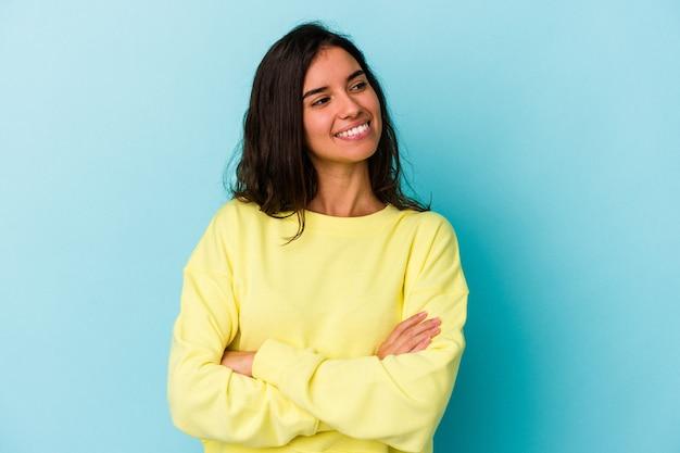 Jonge blanke vrouw geïsoleerd op blauwe achtergrond glimlachend zelfverzekerd met gekruiste armen.