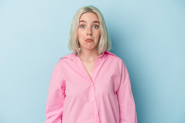 Jonge blanke vrouw geïsoleerd op blauwe achtergrond haalt schouders op en verwarde ogen.