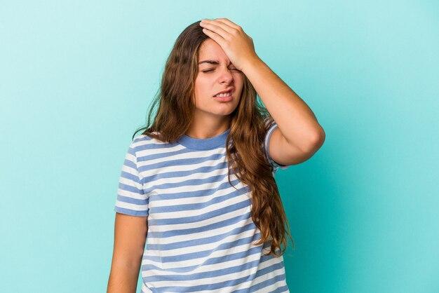 Jonge blanke vrouw geïsoleerd op blauwe achtergrond iets vergeten, voorhoofd slaan met palm en ogen sluiten.