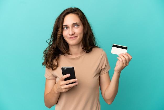 Jonge blanke vrouw geïsoleerd op blauwe achtergrond kopen met de mobiel met een creditcard terwijl ze denken