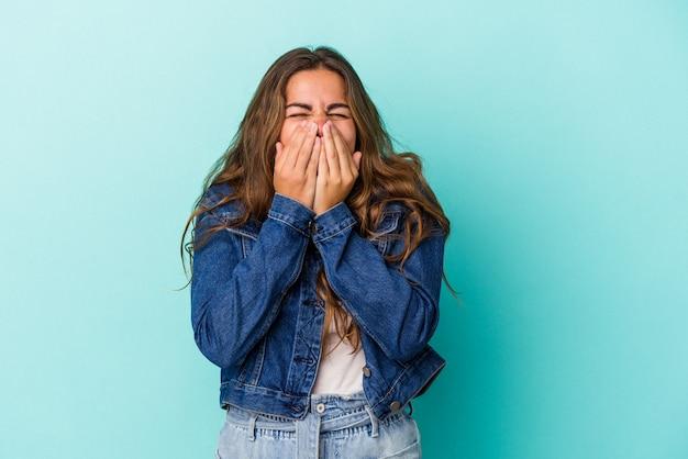 Jonge blanke vrouw geïsoleerd op blauwe achtergrond lachen om iets, mond bedekken met handen.