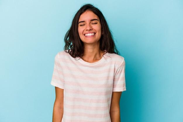 Jonge blanke vrouw geïsoleerd op blauwe achtergrond lacht en sluit de ogen, voelt zich ontspannen en gelukkig.