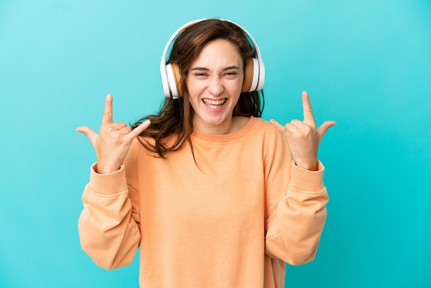 Jonge blanke vrouw geïsoleerd op blauwe achtergrond luisteren muziek maken rock gebaar