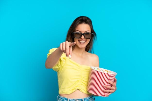 Jonge blanke vrouw geïsoleerd op blauwe achtergrond met 3d-bril en met een grote emmer popcorns terwijl ze naar voren wijst
