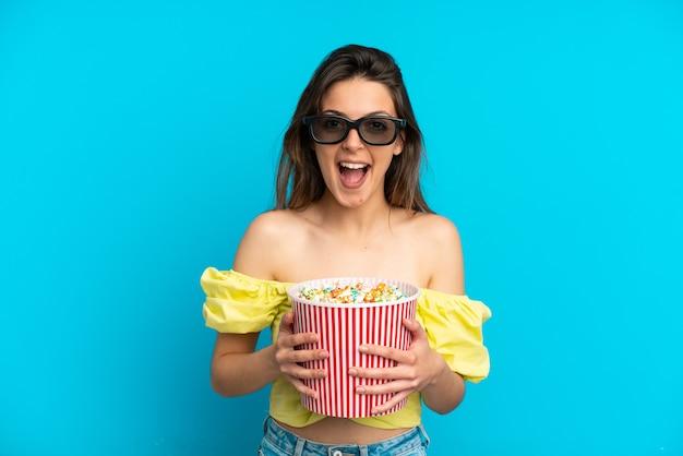 Jonge blanke vrouw geïsoleerd op blauwe achtergrond met 3d-bril en met een grote emmer popcorns