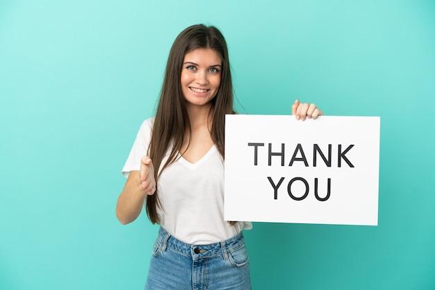 Jonge blanke vrouw geïsoleerd op blauwe achtergrond met een bordje met de tekst bedankt om een deal te sluiten