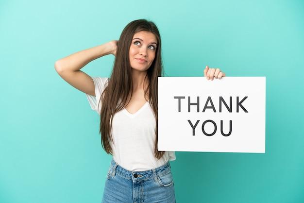 Jonge blanke vrouw geïsoleerd op blauwe achtergrond met een bordje met de tekst dank u en denken