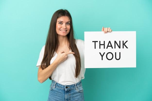 Jonge blanke vrouw geïsoleerd op blauwe achtergrond met een bordje met de tekst dank u en erop wijzend