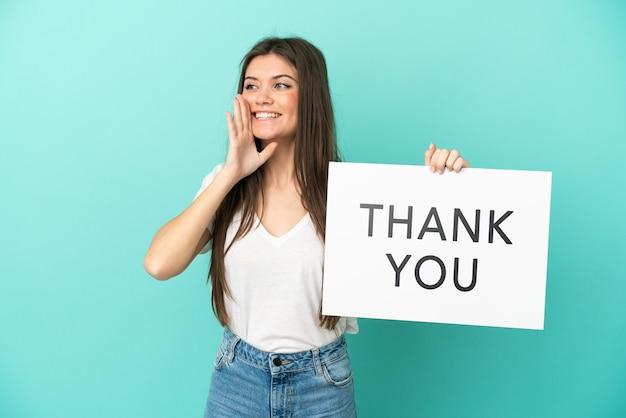 Jonge blanke vrouw geïsoleerd op blauwe achtergrond met een bordje met de tekst dank u en schreeuwen shout