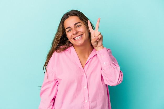 Jonge blanke vrouw geïsoleerd op blauwe achtergrond met nummer twee met vingers.