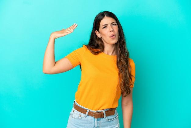 Jonge blanke vrouw geïsoleerd op blauwe achtergrond met vermoeide en zieke expressie
