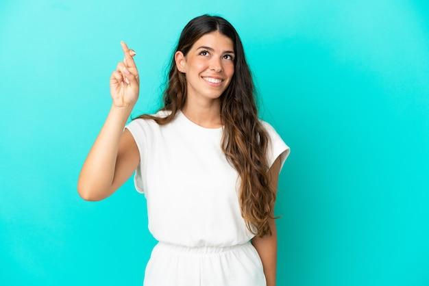 Jonge blanke vrouw geïsoleerd op blauwe achtergrond met vingers die elkaar kruisen en het beste wensen