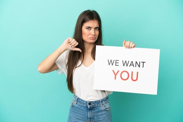 Jonge blanke vrouw geïsoleerd op blauwe achtergrond met we want you board met trots gebaar