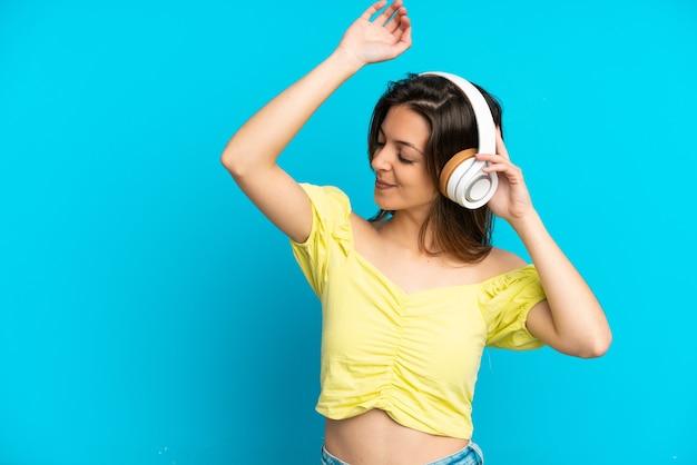 Jonge blanke vrouw geïsoleerd op blauwe achtergrond muziek luisteren en dansen
