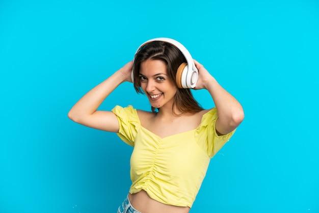 Jonge blanke vrouw geïsoleerd op blauwe achtergrond muziek luisteren