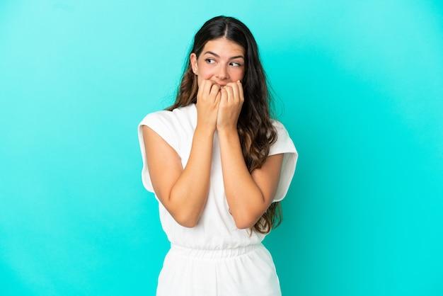 Jonge blanke vrouw geïsoleerd op blauwe achtergrond nerveus en bang om de handen in de mond te leggen
