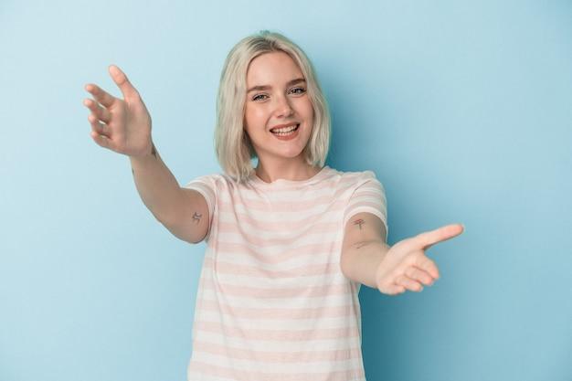 Jonge blanke vrouw geïsoleerd op blauwe achtergrond voelt zich zelfverzekerd en geeft een knuffel aan de camera.