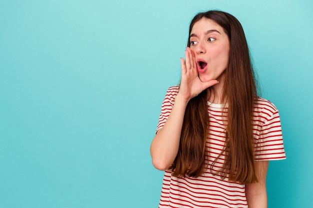 Jonge blanke vrouw geïsoleerd op blauwe achtergrond zegt een geheim heet remnieuws en kijkt opzij