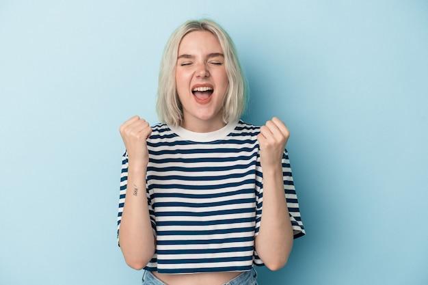 Jonge blanke vrouw geïsoleerd op blauwe achtergrond zorgeloos en opgewonden juichen. overwinningsconcept.