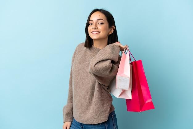 Jonge blanke vrouw geïsoleerd op blauwe muur met boodschappentassen en glimlachen