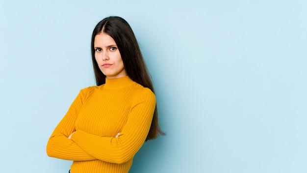 Jonge blanke vrouw geïsoleerd op blauwe muur verdacht, onzeker, onderzoekt u.