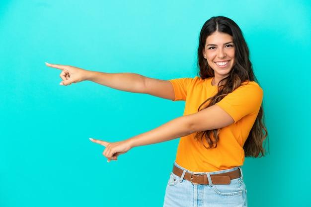 Jonge blanke vrouw geïsoleerd op een blauwe achtergrond die met de vinger naar de zijkant wijst en een product presenteert