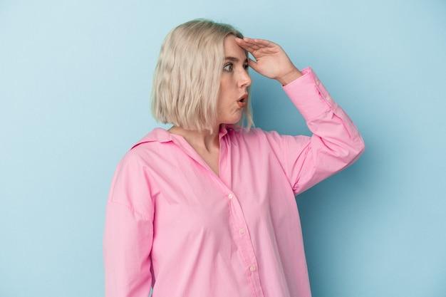 Jonge blanke vrouw geïsoleerd op een blauwe achtergrond die ver weg kijkt en hand op het voorhoofd houdt.