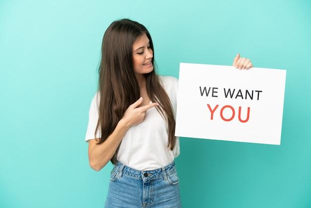 Jonge blanke vrouw geïsoleerd op een blauwe achtergrond die we want you aan boord houdt en erop wijst