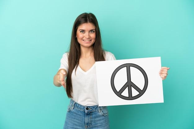 Jonge blanke vrouw geïsoleerd op een blauwe achtergrond met een bordje met vredessymbool die een deal maakt
