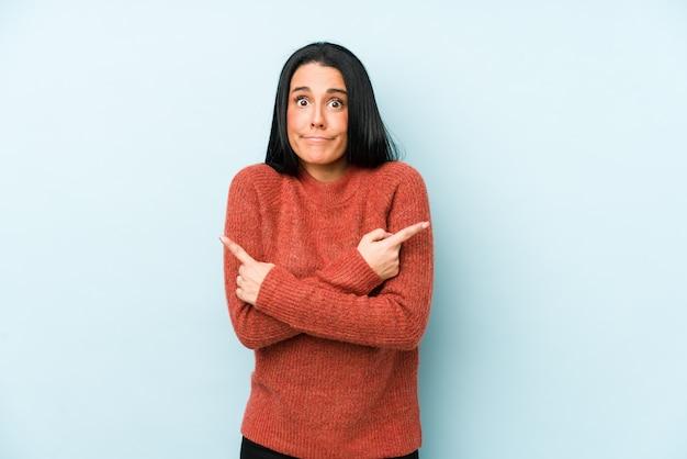 Jonge blanke vrouw geïsoleerd op een blauwe muur wijst zijwaarts, probeert te kiezen tussen twee opties.