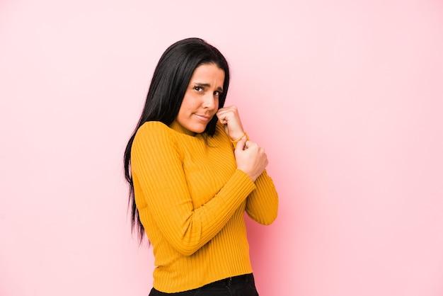 Jonge blanke vrouw geïsoleerd op een roze ruimte bang en bang.