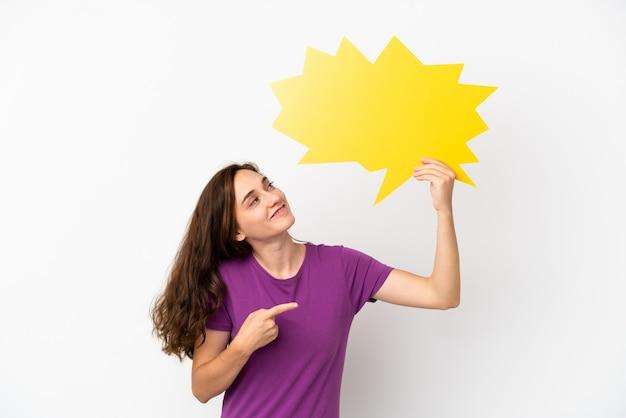 Jonge blanke vrouw geïsoleerd op een witte achtergrond die een lege tekstballon houdt en erop wijst
