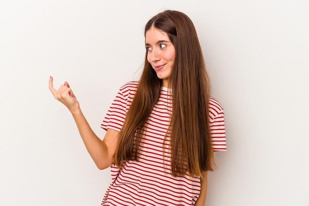 Jonge blanke vrouw geïsoleerd op een witte achtergrond die met de vinger naar je wijst alsof uitnodigend dichterbij komt.
