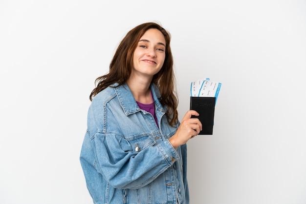 Jonge blanke vrouw geïsoleerd op een witte achtergrond gelukkig in vakantie met paspoort en vliegtickets