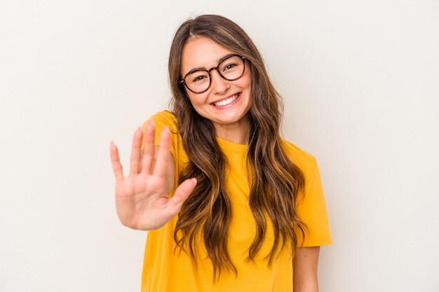 Jonge blanke vrouw geïsoleerd op een witte achtergrond glimlachend vrolijk weergegeven: nummer vijf met vingers.