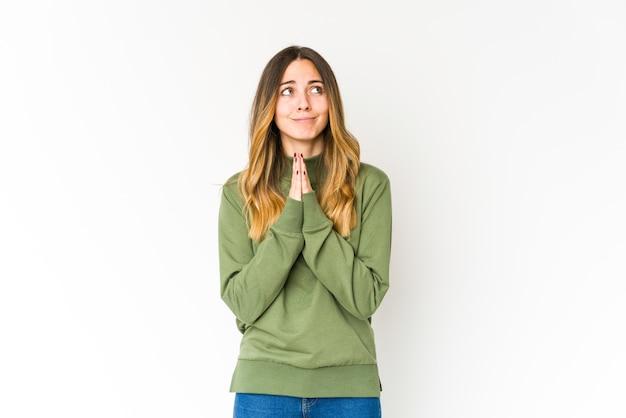 Jonge blanke vrouw geïsoleerd op een witte achtergrond hand in hand bidden in de buurt van de mond, voelt zich zelfverzekerd.