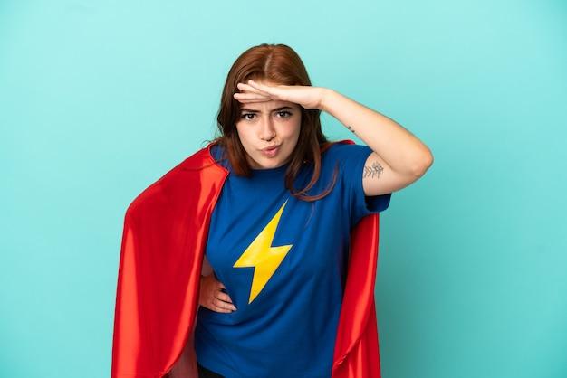 Jonge blanke vrouw geïsoleerd op een witte achtergrond in superheld kostuum en iets tonen