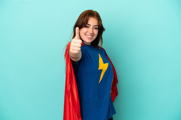 Jonge blanke vrouw geïsoleerd op een witte achtergrond in superheld kostuum met duim omhoog