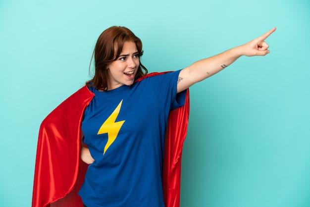 Jonge blanke vrouw geïsoleerd op een witte achtergrond in superheld kostuum met trots gebaar