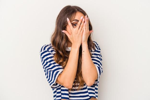 Jonge blanke vrouw geïsoleerd op een witte achtergrond knipperen door vingers bang en nerveus.