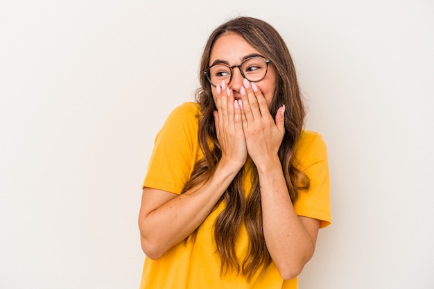 Jonge blanke vrouw geïsoleerd op een witte achtergrond lachen om iets, mond bedekken met handen.
