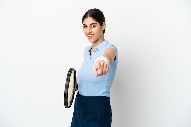 Jonge blanke vrouw geïsoleerd op een witte achtergrond tennissen en wijzend naar voren
