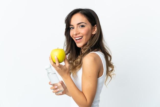 Jonge blanke vrouw geïsoleerd op een witte muur met een appel en met een fles water