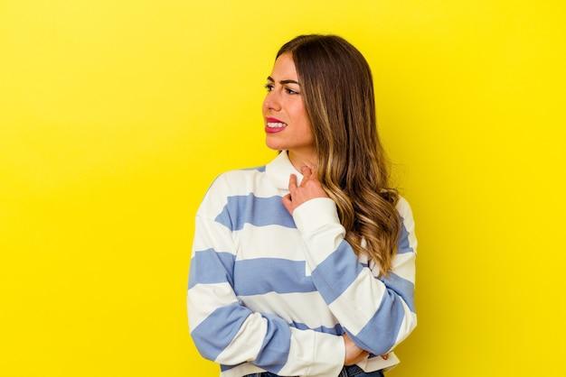 Jonge blanke vrouw geïsoleerd op geel lijdt pijn in de keel als gevolg van een virus of infectie.