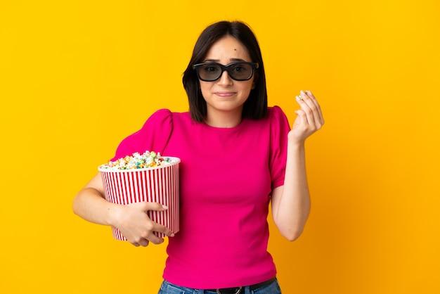 Jonge blanke vrouw geïsoleerd op geel met 3d-bril en met een grote emmer popcorn