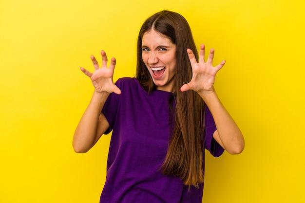 Jonge blanke vrouw geïsoleerd op gele achtergrond boos schreeuwen met gespannen handen.