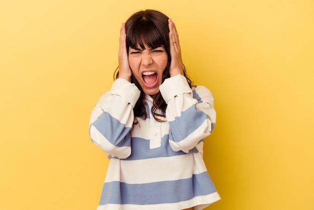 Jonge blanke vrouw geïsoleerd op gele achtergrond die oren bedekt met handen die proberen niet te hard geluid te horen.