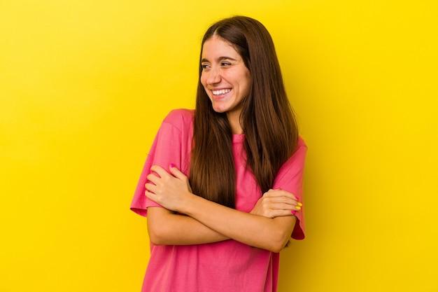 Jonge blanke vrouw geïsoleerd op gele achtergrond glimlachend zelfverzekerd met gekruiste armen.